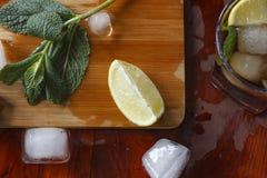 Ингридиенты для спиртного коктеиля: лед, мята, лимон, известка Ром, виски, коньяк Стоковые Изображения