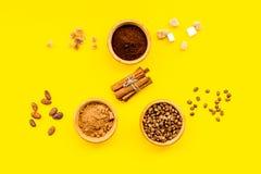 Ингридиенты для хлебопекарни и десертов Циннамон, какао, кофе, сахар, специи на желтом взгляд сверху предпосылки Стоковые Изображения