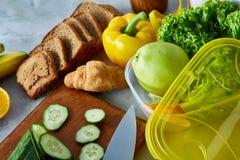 Ингридиенты для школьного обеда и пластмасового контейнера на таблице, конца-вверх, селективного фокуса Стоковые Фото
