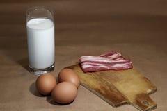 Ингридиенты омлета с яичками, молока, бекона на деревянном крупном плане разделочной доски Стоковое Фото