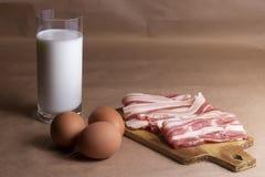 Ингридиенты омлета с яичками, молока, бекона на деревянном крупном плане разделочной доски Стоковые Фото