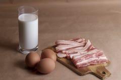 Ингридиенты омлета с яичками, молока, бекона на деревянном крупном плане разделочной доски Стоковые Изображения