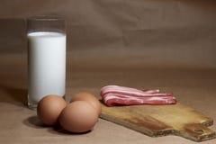 Ингридиенты омлета с яичками, молока, бекона на деревянном крупном плане разделочной доски Стоковое фото RF