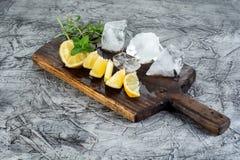 Ингридиент коктеиля: Мята и лимон лета для освежая mojito коктеиля с льдом на кухне всходят на борт Стоковое фото RF