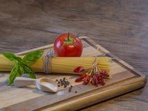 Ингридиент pepperoni спагетти на деревянной прерывая доске красной и Стоковая Фотография RF