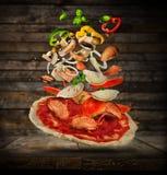 Ингридиенты летания с тестом пиццы, на деревянной предпосылке Стоковые Изображения RF