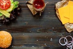 Ингридиенты и соус бургера с космосом экземпляра на деревянной черной таблице Стоковые Изображения