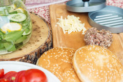 Ингридиенты для варить бургеры Сырцовые котлеты мяса говяжего фарша на деревянной прерывая доске, красном луке, томатах вишни, зе Стоковые Фотографии RF