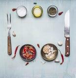 Ингридиенты для варить, приправляя, масло, нож, вилка, чеснок, горячий красный пеец, выровнянная рамка на деревянных деревенских  Стоковые Изображения RF