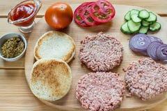 Ингридиенты для гамбургера на деревянной разделочной доске Стоковые Изображения RF