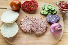 Ингридиенты для гамбургера на деревянной разделочной доске Стоковое Фото