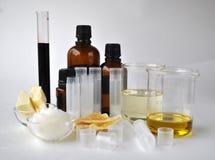 Ингридиенты для делать естественные масло, кокос, миндалину, жожобу и эфирные масла какао косметик с трубками и бутылками стоковое фото rf