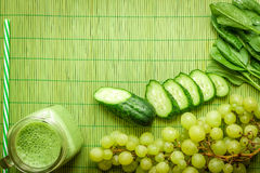 Ингридиенты для зеленого smoothie вытрезвителя Шпинат, виноградина, огурец на зеленой предпосылке Стоковые Фото