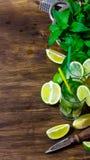 Ингридиенты для известок коктеиля, рома, листьев мяты, кубов льда на деревянном столе Стоковые Фото