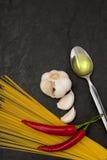Ингридиенты для olio aglio e спагетти на черной предпосылке камня шифера Стоковое Изображение