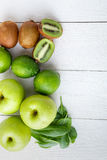 Ингридиенты для smoothie Зеленый цвет приносить на белой деревянной предпосылке Яблоко, известка, шпинат, киви Вытрезвитель еда з стоковые изображения