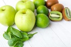 Ингридиенты для smoothie Зеленый цвет приносить на белой деревянной предпосылке Яблоко, известка, шпинат, киви Вытрезвитель еда з стоковые фотографии rf