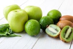 Ингридиенты для smoothie Зеленый цвет приносить на белой деревянной предпосылке Яблоко, известка, шпинат, киви Вытрезвитель еда з Стоковое Изображение