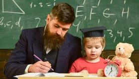 Индивидуальный урок с первым грейдером Учитель и зрачок в mortarboard в классе, доске на предпосылке индивидуально стоковое фото rf