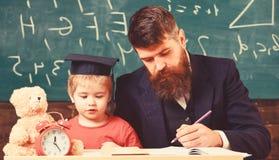 Индивидуальный урок с первым грейдером Учитель и зрачок в mortarboard в классе, доске на предпосылке Индивидуальный стоковое фото