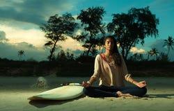 Индийская девушка серфера размышляя в представлении лотоса на пляж на заходе солнца рядом с surfboard стоковые фотографии rf