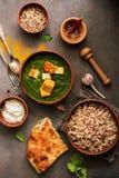 Индийская еда Palak Paneer, naan хлеб, рис и специи на темной предпосылке Взгляд сверху, плоское положение, космос экземпляра стоковые фотографии rf
