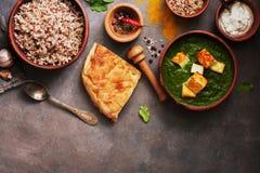 Индийская еда Palak Paneer, naan хлеб, рис и специи на темной предпосылке Надземный взгляд, космос экземпляра стоковые фотографии rf