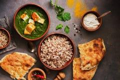 Индийская еда Palak Paneer, naan хлеб, рис и специи на темной предпосылке r r стоковые фото