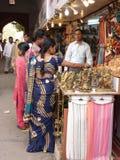 Индийские женщины в цветастых сари просматривают рынок стоковые изображения rf