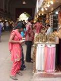 Индийские женщины в цветастых сари просматривают рынок стоковые изображения