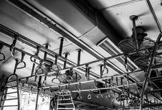 Индийские интерьеры поезда в черно-белом: стальные ручки и вентиляторы; винтажный и ретро стоковые фотографии rf