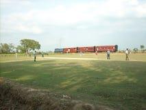 Индийский железнодорожный поезд с полем и игроками сверчка стоковое фото rf