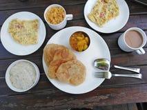 Индийский завтрак - хлеб, специи, omlet, чай masala, хлопья мозоли с молоком стоковая фотография