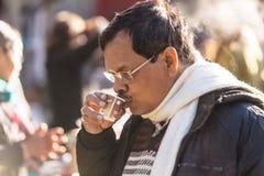 Индийский парень выпивая бумажный стаканчик индийского чая в рынке около холма тигра в зиме на Darjeeling, Индии Стоковые Изображения