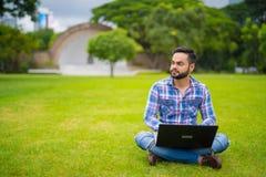 Индийский человек в парке используя портативный компьютер и думать стоковое фото rf
