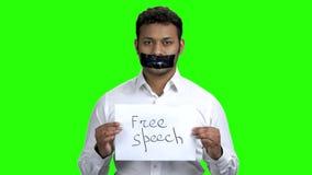 Индийский человек со связанным тесьмой ртом на зеленом экране