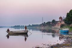 2 индийских люд плавают старой деревянной шлюпкой Стоковые Фотографии RF