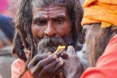 Индийское sadhus освещая вверх и куря Ganja Стоковая Фотография