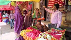 Индия, Варанаси, 10-ое марта 2019 - человек с женщинами продевая нитку и обсуждая красочные гирлянды цветка и индусские предложен видеоматериал
