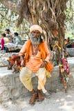 ИНДИЯ, LAXMAN JHULA - 15-ОЕ АПРЕЛЯ 2017: Sadhu сидя на реке Стоковые Фотографии RF