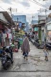 Индонезийская мусульманская женщина нося вуаль идет вниз с заднего переулка в Джакарте, Индонезии стоковое фото rf