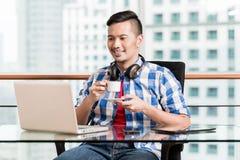 Индонезийская профессиональная работа на компьтер-книжке имея кофе Стоковые Изображения