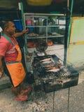 Индонезийский уличный торговец продавая зажаренных рыб Стоковое Изображение