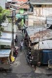 Индонезийский человек идет вниз с заднего переулка в Джакарте, Индонезии стоковая фотография rf
