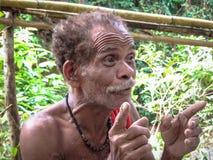 Индонезия тюкованный Лето 2015 Человек Korowai говорит жестикулировать с его руками стоковые фотографии rf