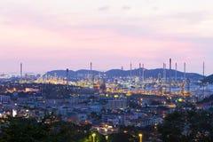 Индустриальная зона нефтеперерабатывающего предприятия на заходе солнца Стоковые Фото