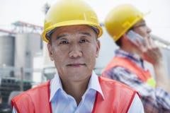 2 инженера в защитной деятельности workwear, смотря камеру, вне фабрики Стоковая Фотография RF