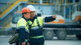 2 инженера молодого человека disussing на фабрике масла сток-видео