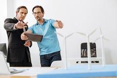 2 инженера обсуждая размер модели станции энергии ветра Стоковая Фотография