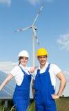 2 инженера представляя с ветротурбиной и панелями солнечных батарей Стоковые Фотографии RF